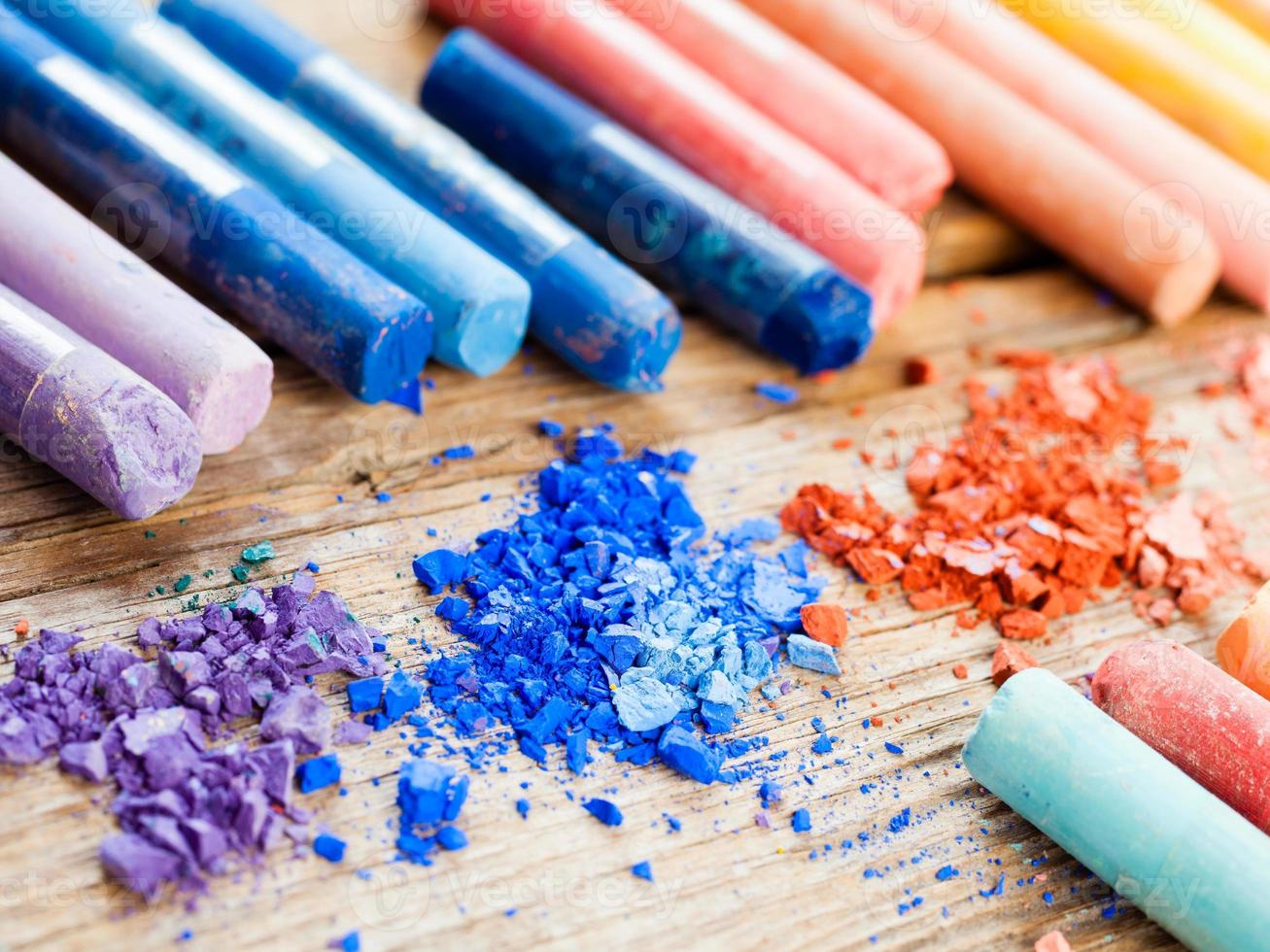 Rainbow colored pastel crayons with crushed chalk close up photo