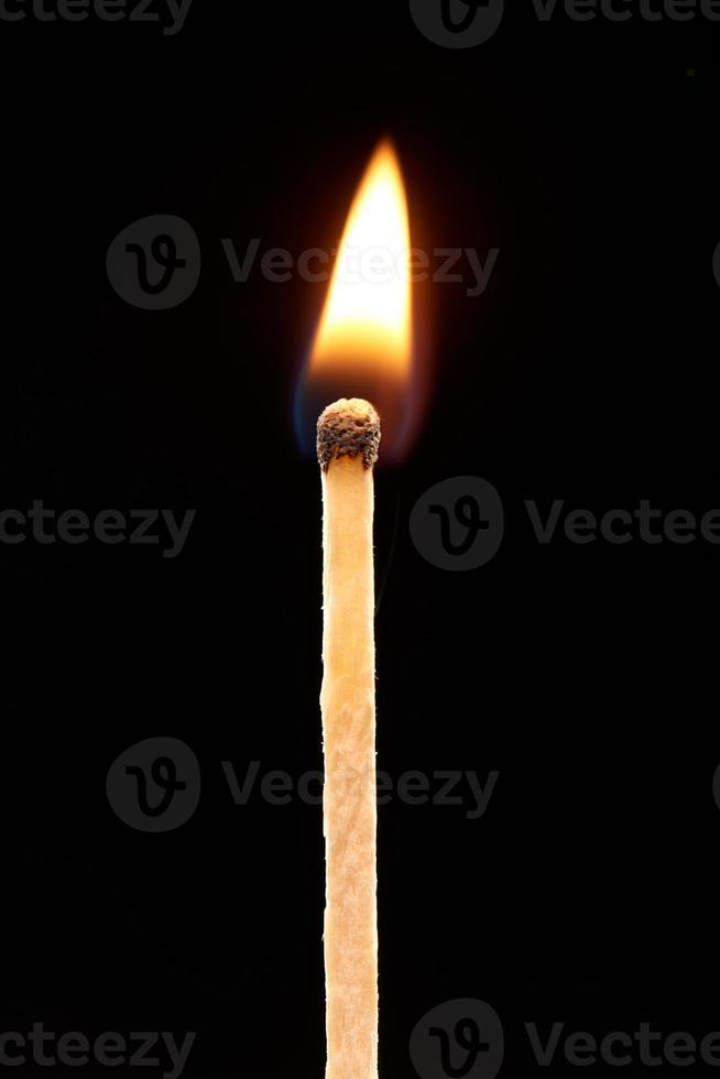 Burning match isolated on black background photo