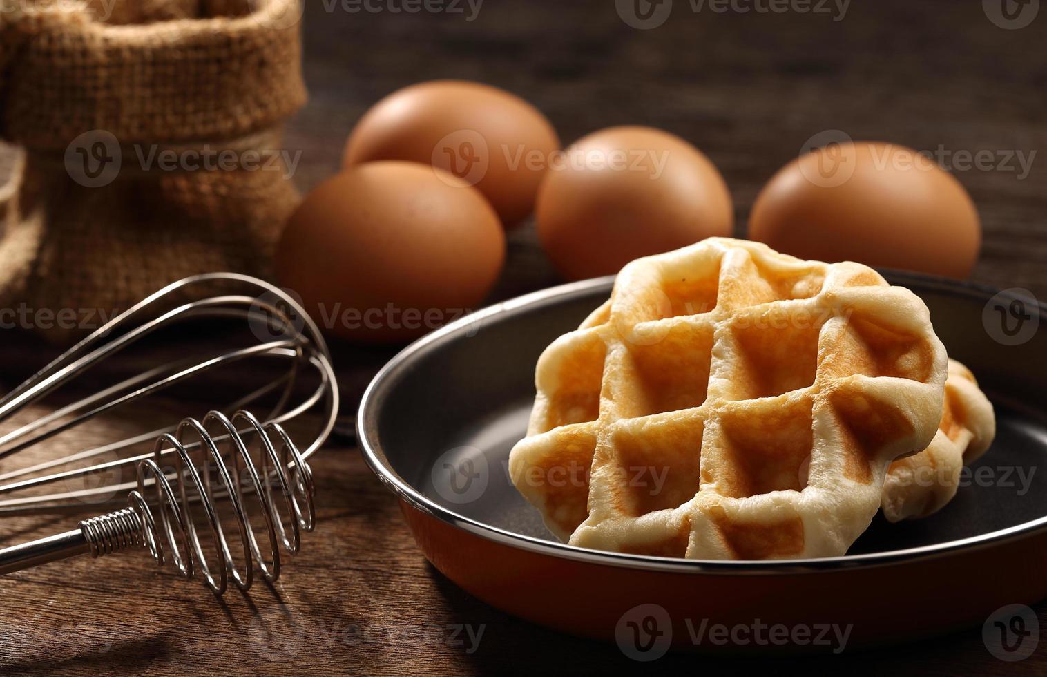 cerrar waffles dentro de una sartén de teflón con batidor y huevos foto