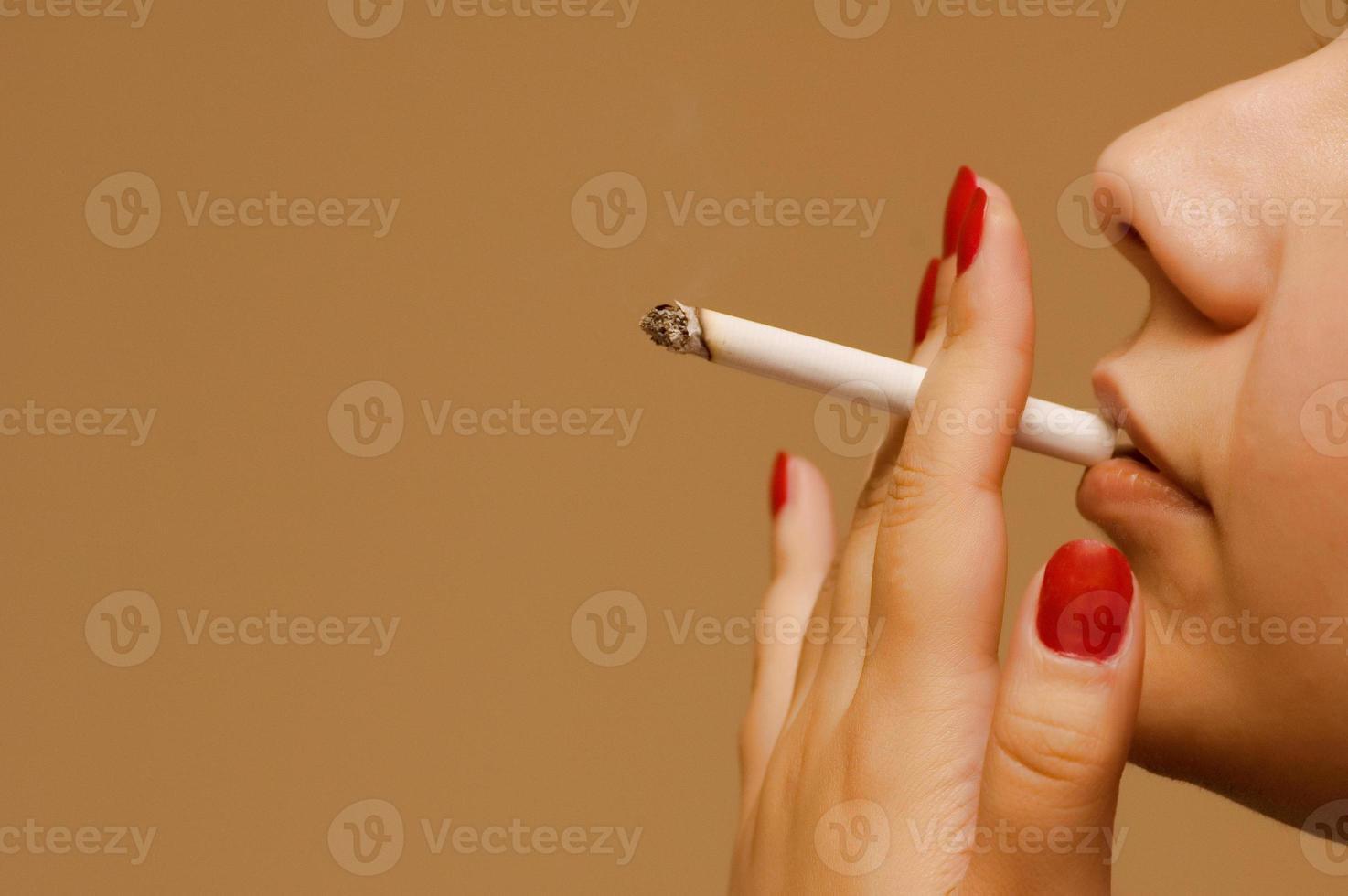 mujer fumando el cigarrillo sobre fondo naranja foto