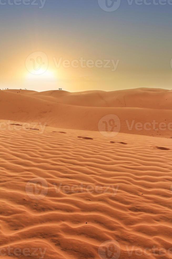 puesta de sol en paisajes desérticos, huellas en arena ondulada foto