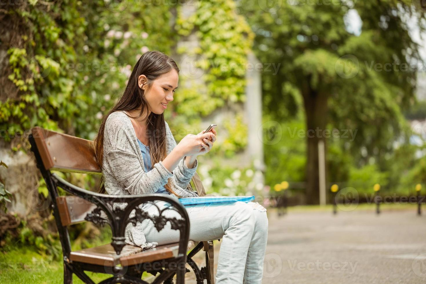 Smiling student sitting on bench in college photo