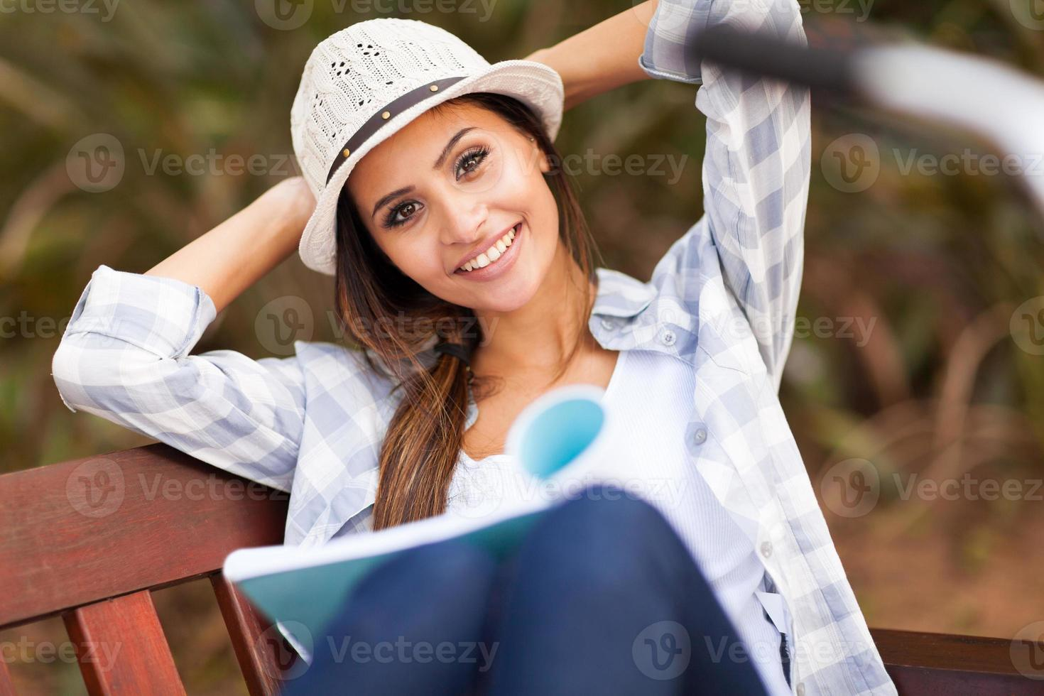 pretty college student reading book at the park photo