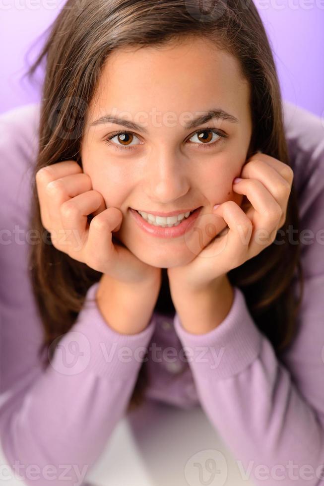 Teenager-Mädchen, das auf lila Nahaufnahmeporträt lächelt foto