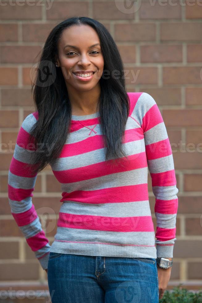 muy feliz mujer afroamericana estudiante universitaria en el campus foto