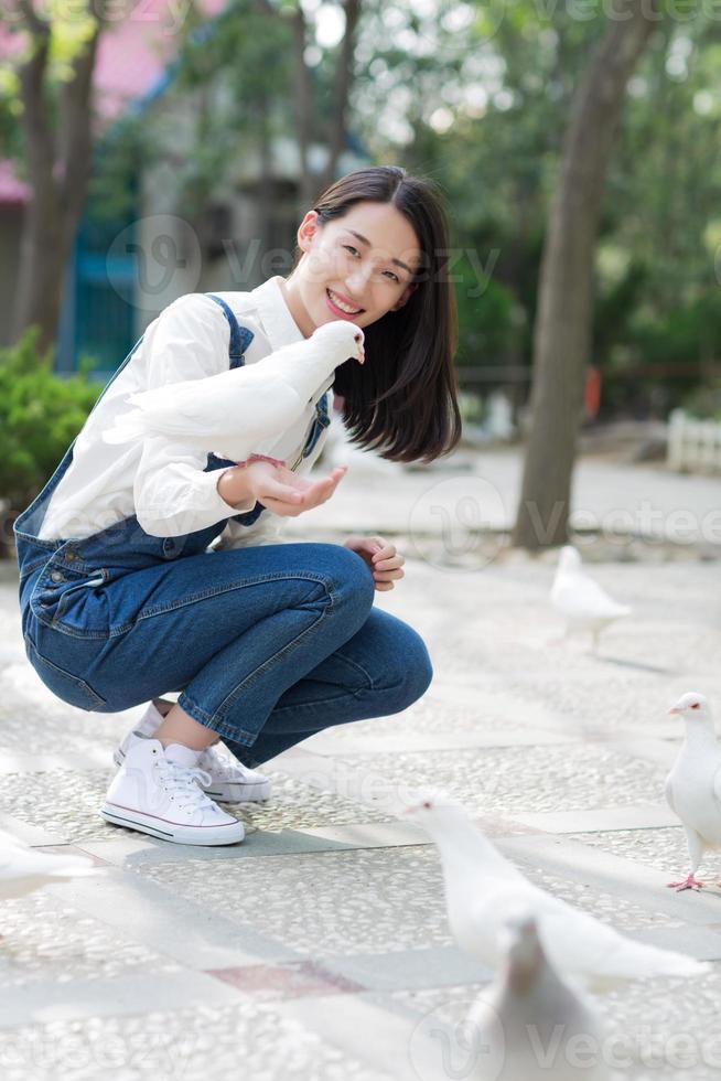 niña alimentando palomas foto