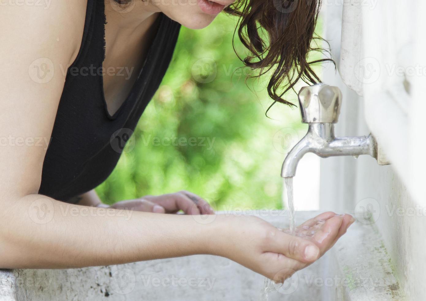 mujer agua potable en el parque foto