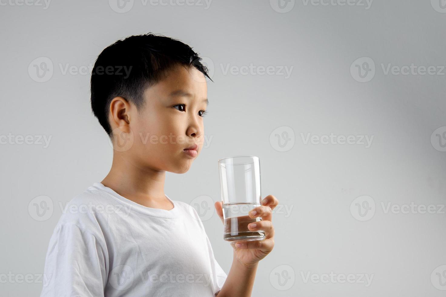niño bebe agua de vidrio foto