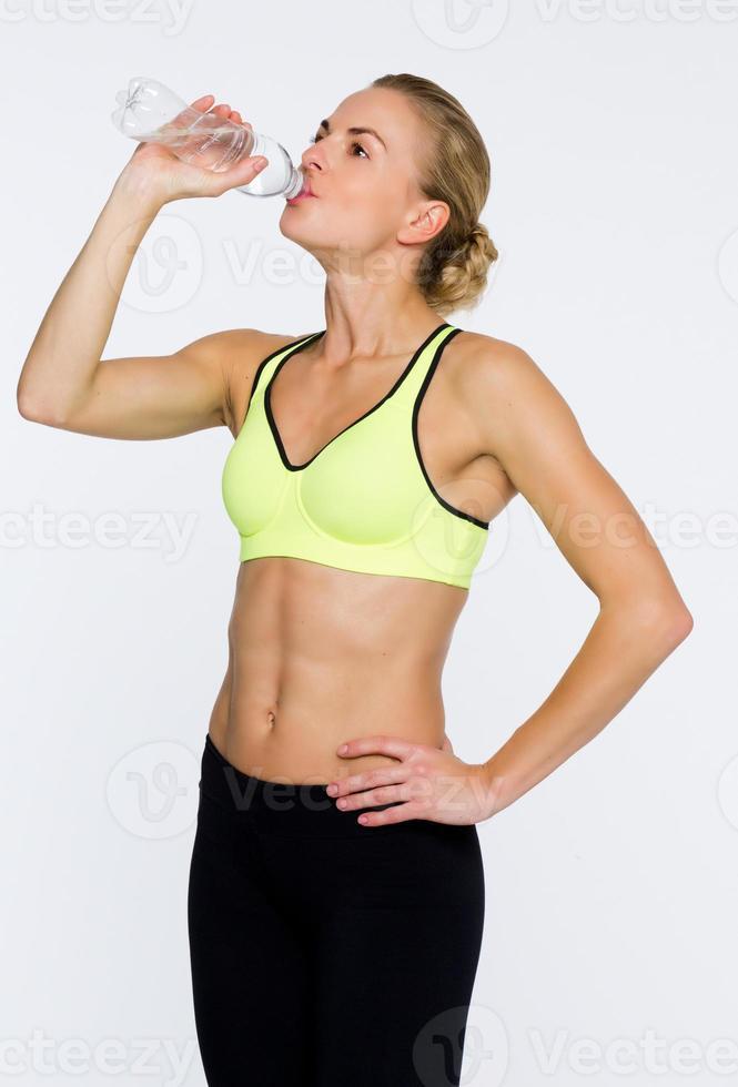 Beautiful fitness coach drinking water photo