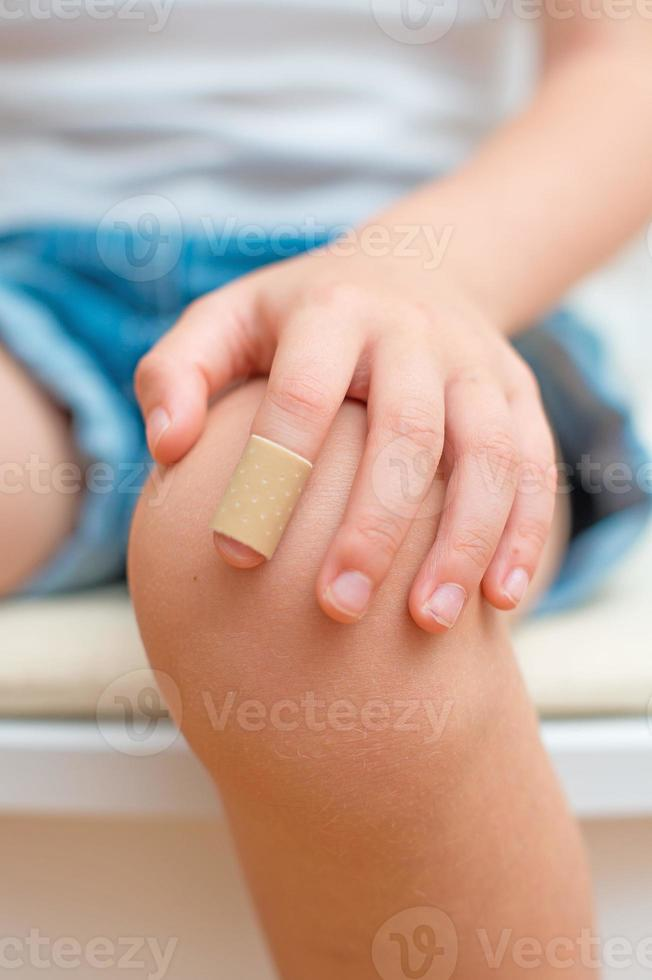 Child finger with an adhesive bandage. photo