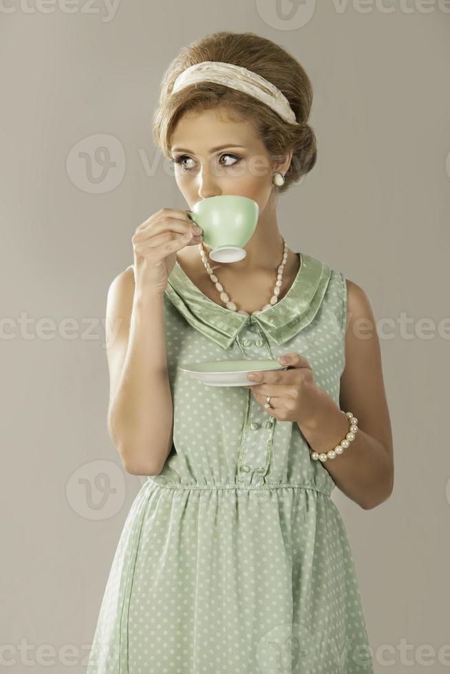 mujer retro de los años cincuenta bebiendo té foto