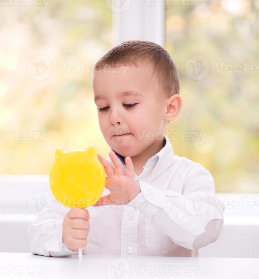niño pequeño con piruleta foto