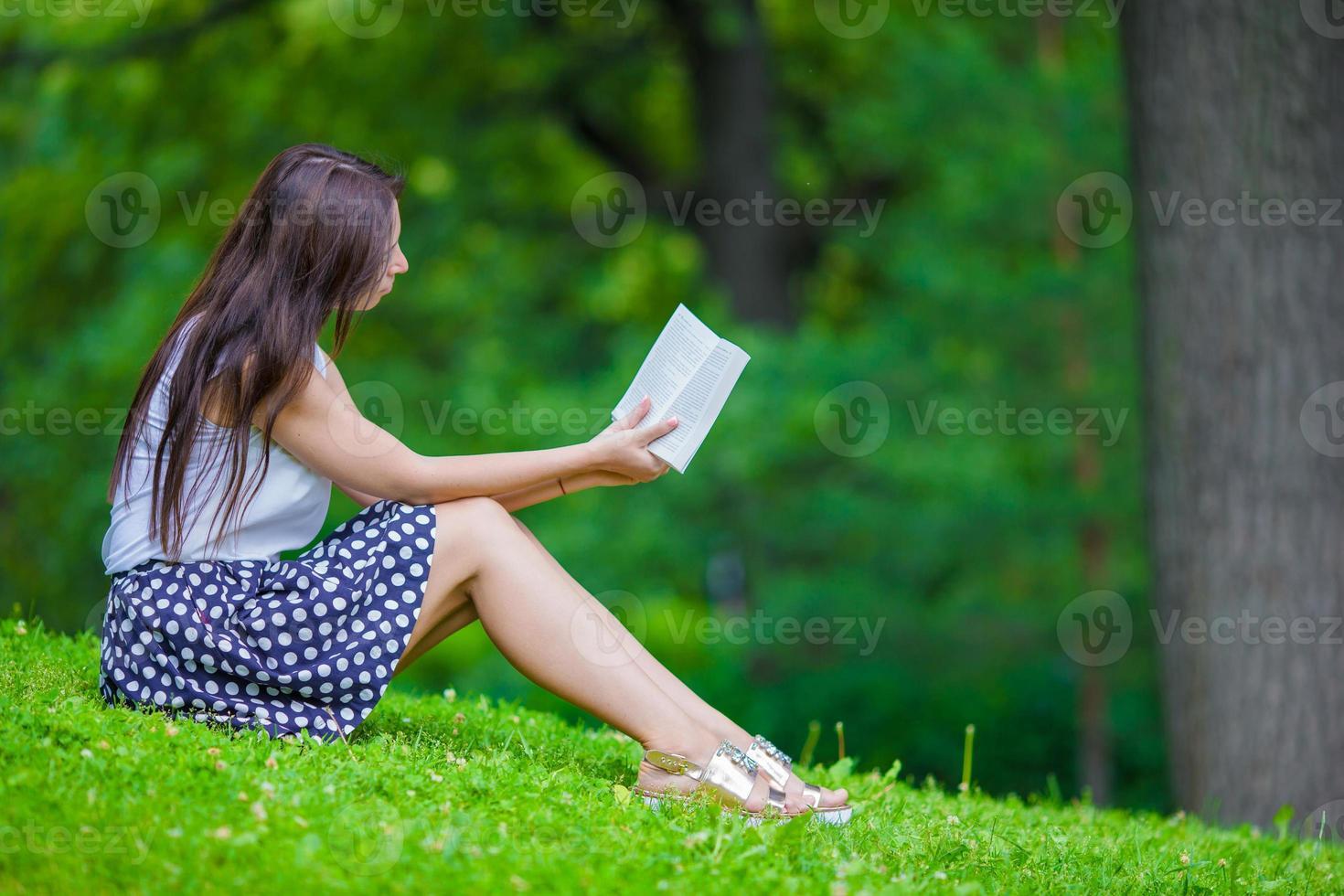 Niña leyendo un libro afuera en el parque foto