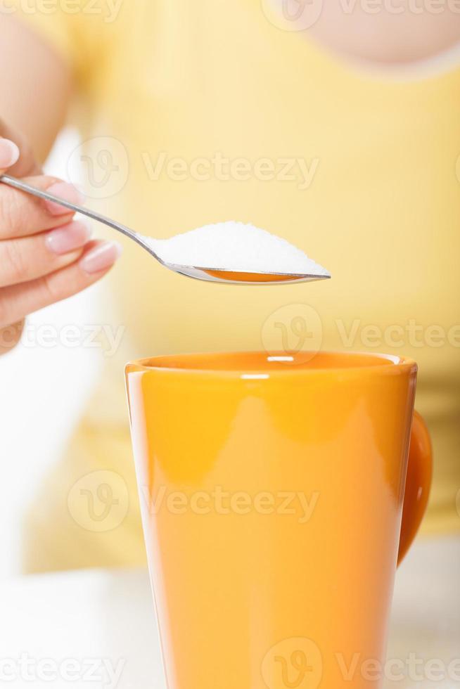 Woman sweetening drink photo