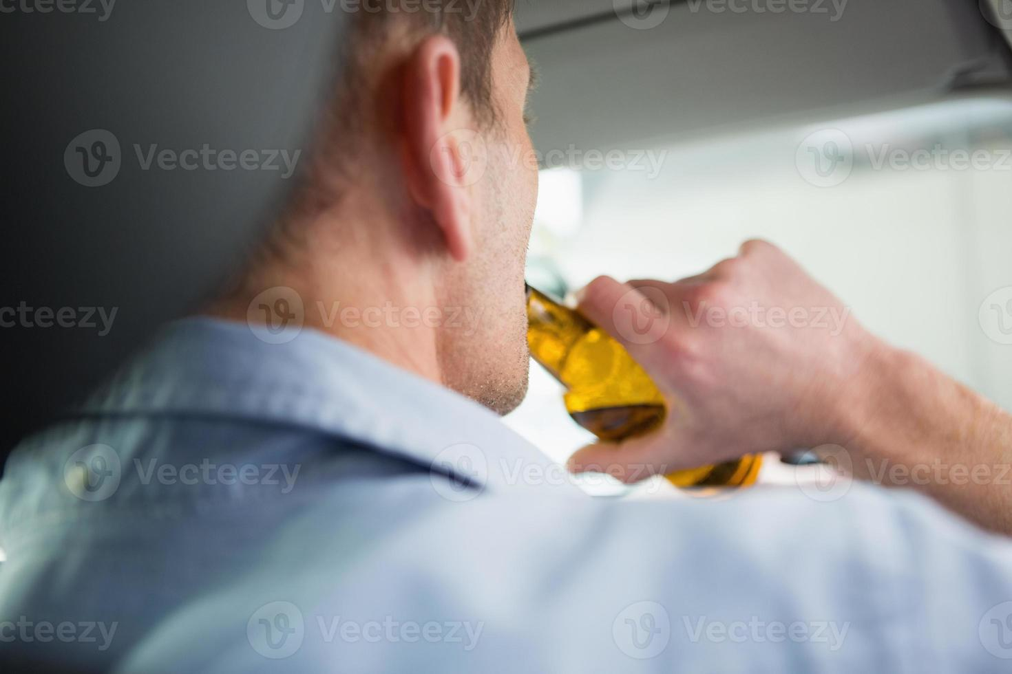 Man drinking beer while driving photo