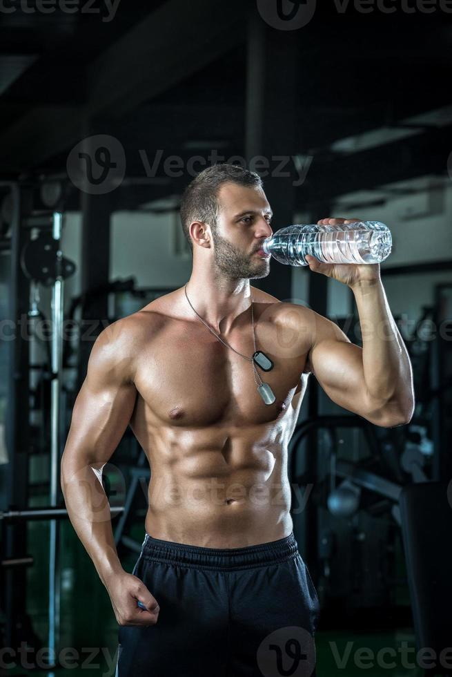 hombre agua potable en gimnasio foto