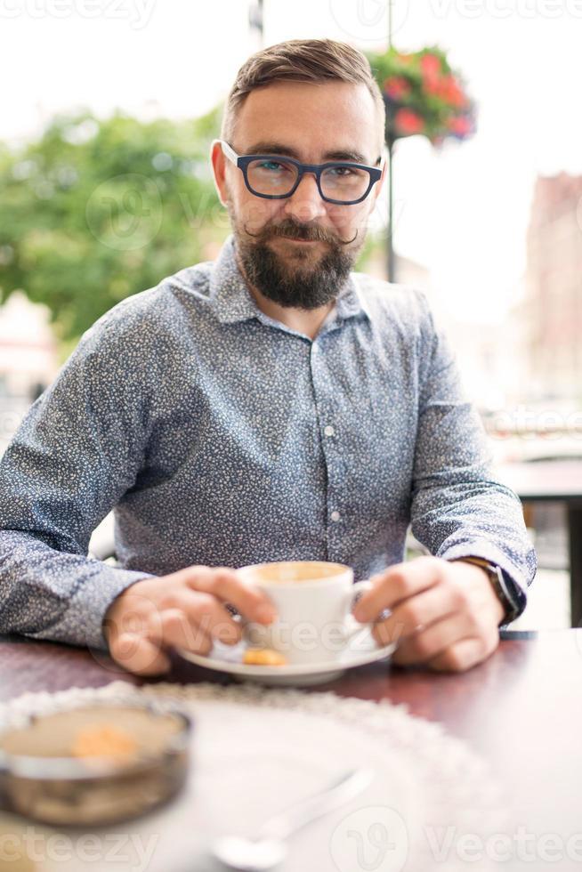 Elegant man drinking coffee outdoors photo