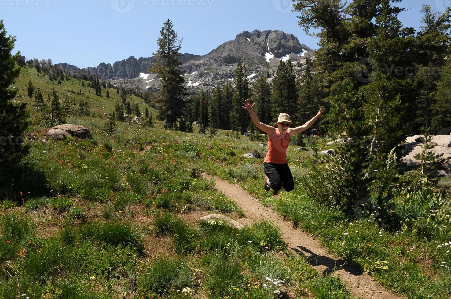 mujer saltando sobre una ruta de senderismo foto