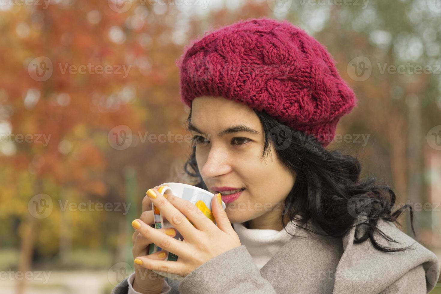 mooie vrouw het drinken van thee buitenshuis foto