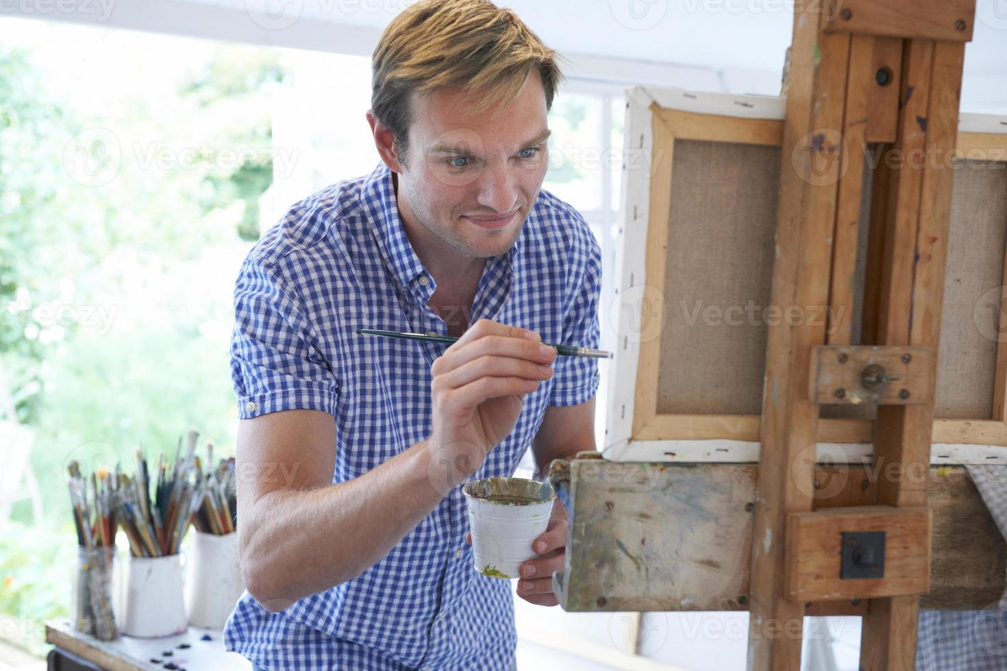 Male Artist Painting In Studio photo
