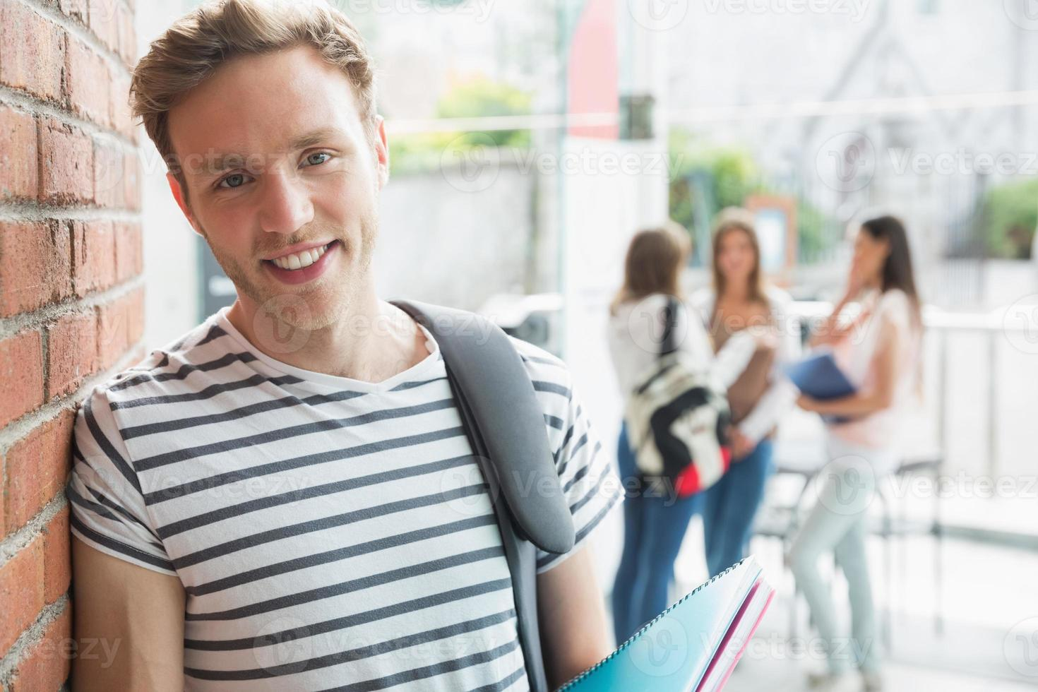 Handsome student smiling and holding notepads photo