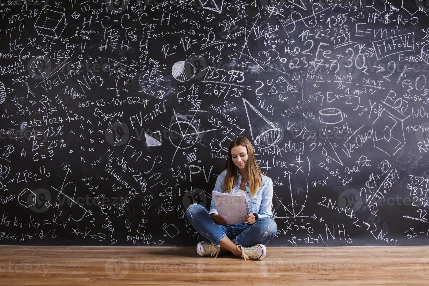 Beautiful young girl in front of blackboard photo