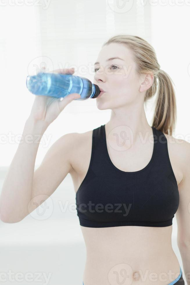 Woman drinking water during workout photo