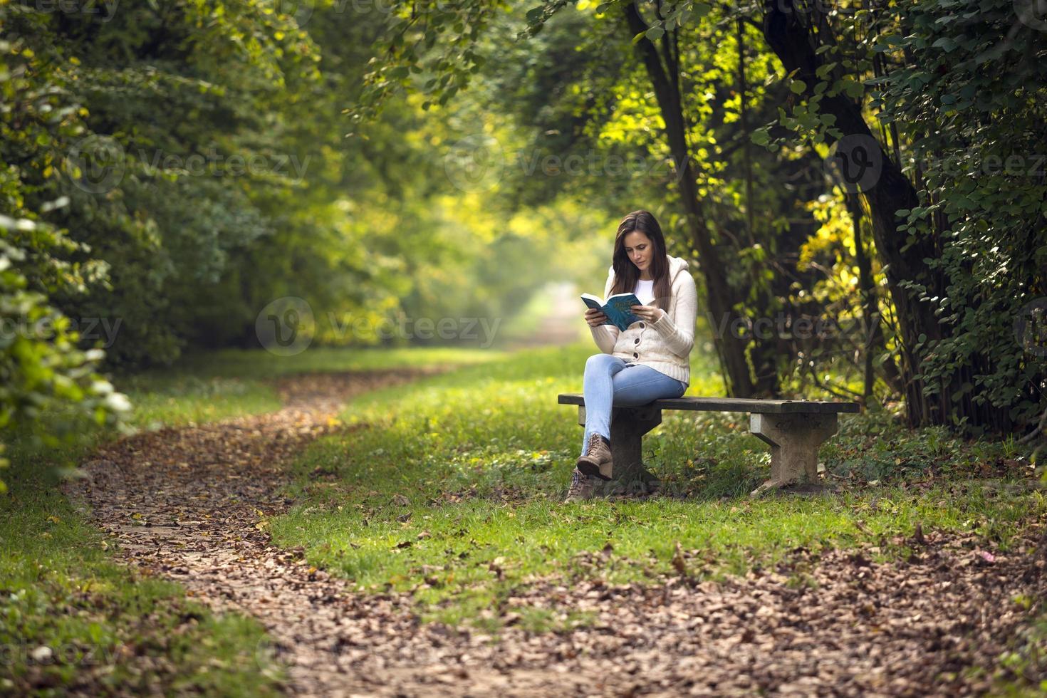 hermosa niña sentada en un banco del parque foto