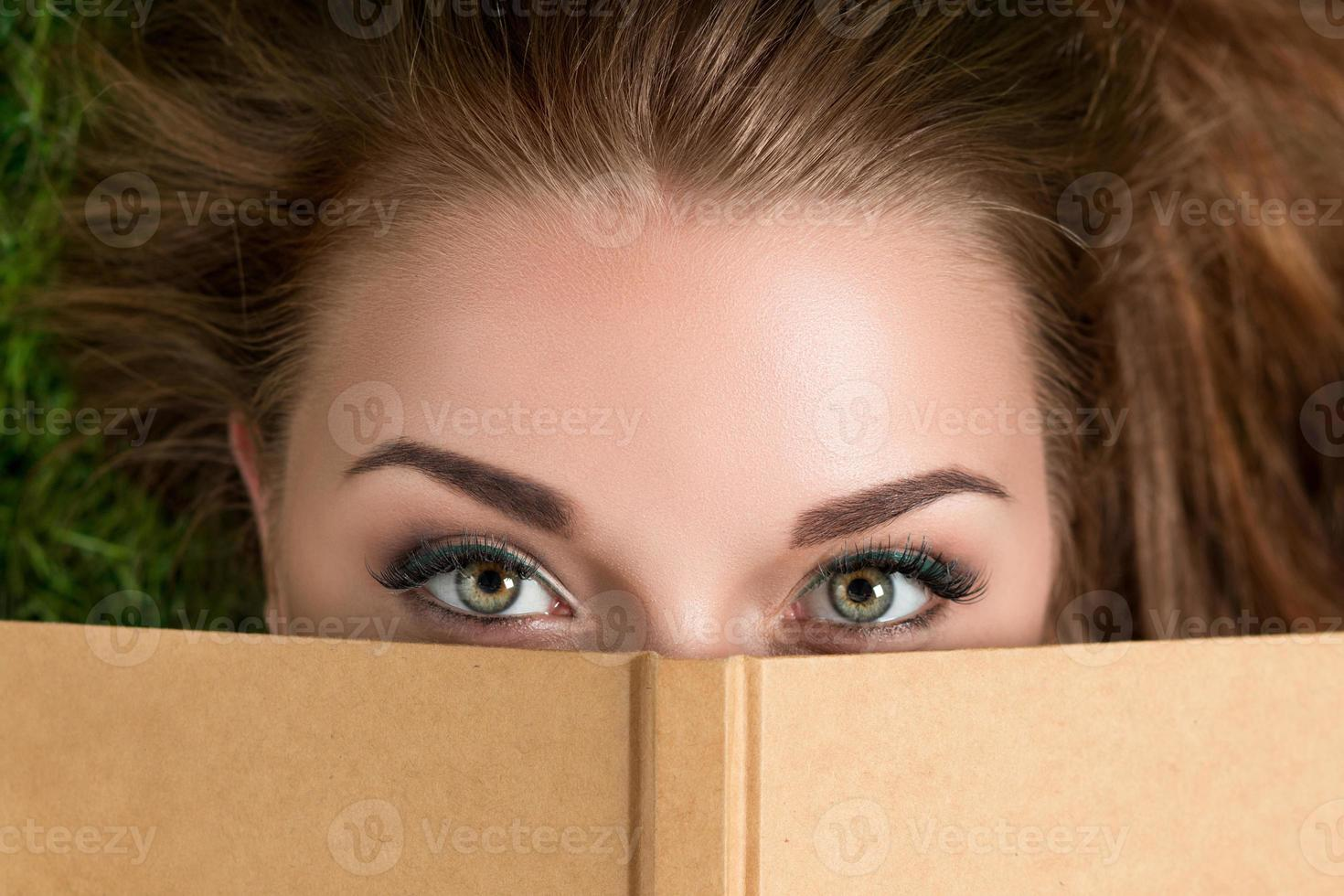 Beautiful young woman looking over book cover photo
