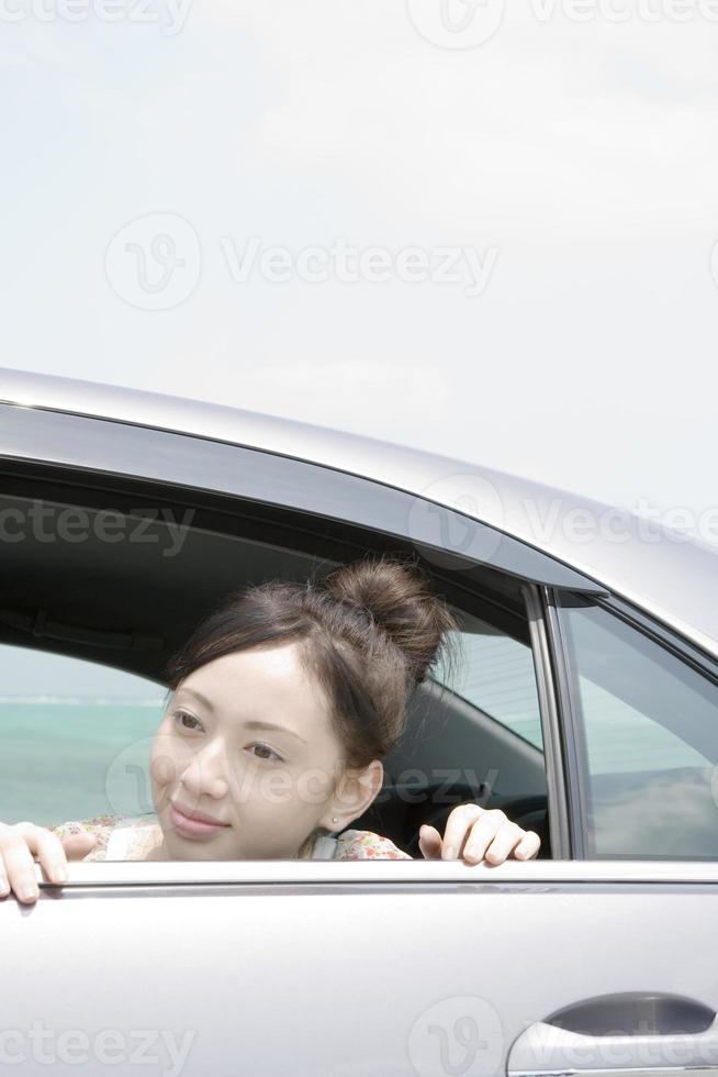 Woman leaning out from backseat of car photo