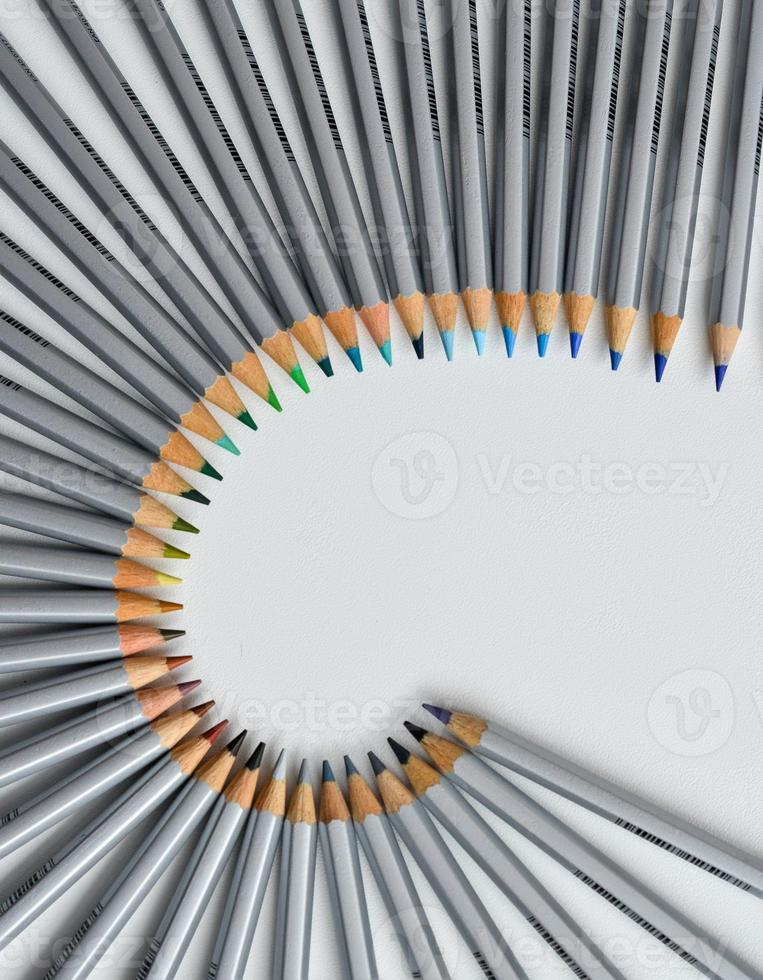 Colorful pencils arranged in a wave isolated over white  background photo