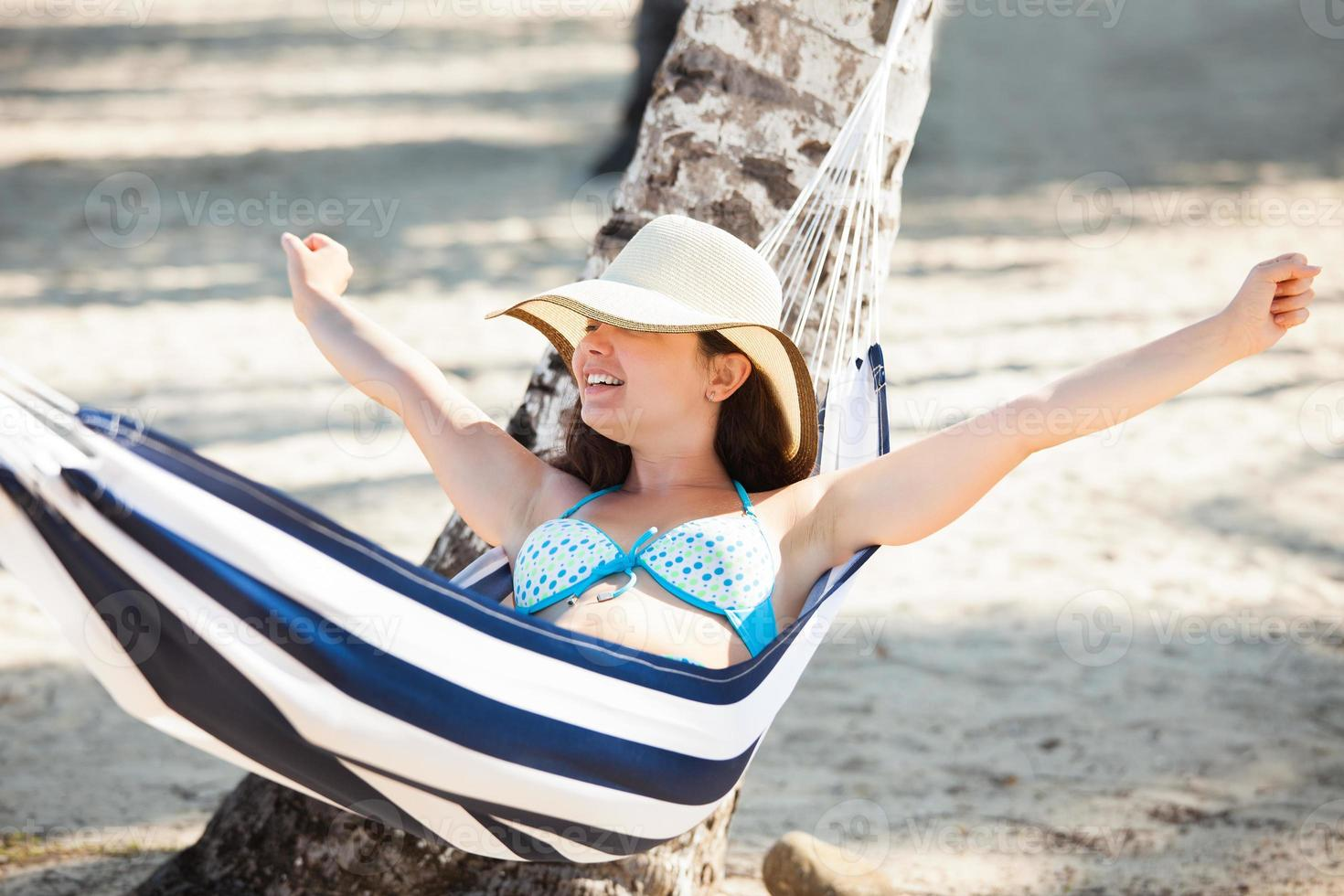 Woman Stretching In Hammock At Beach photo