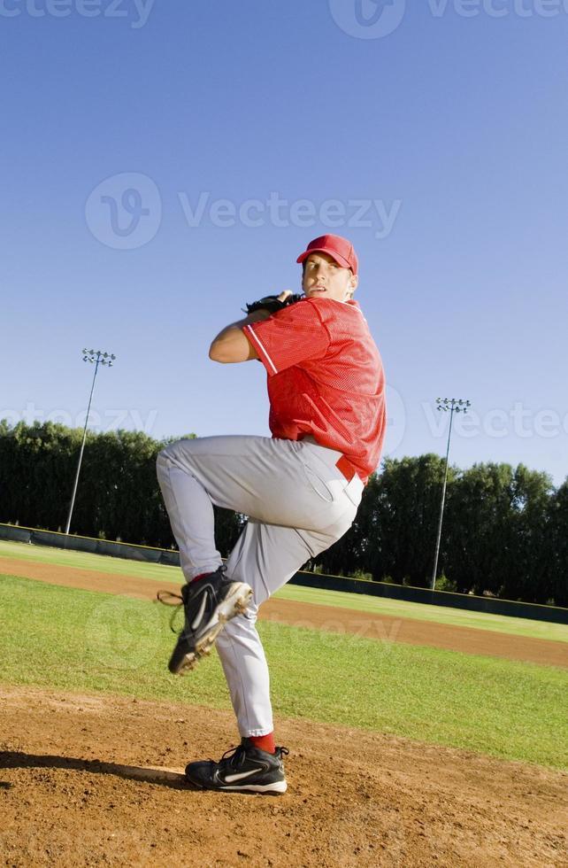 lanzador de béisbol lanzando un lanzamiento foto