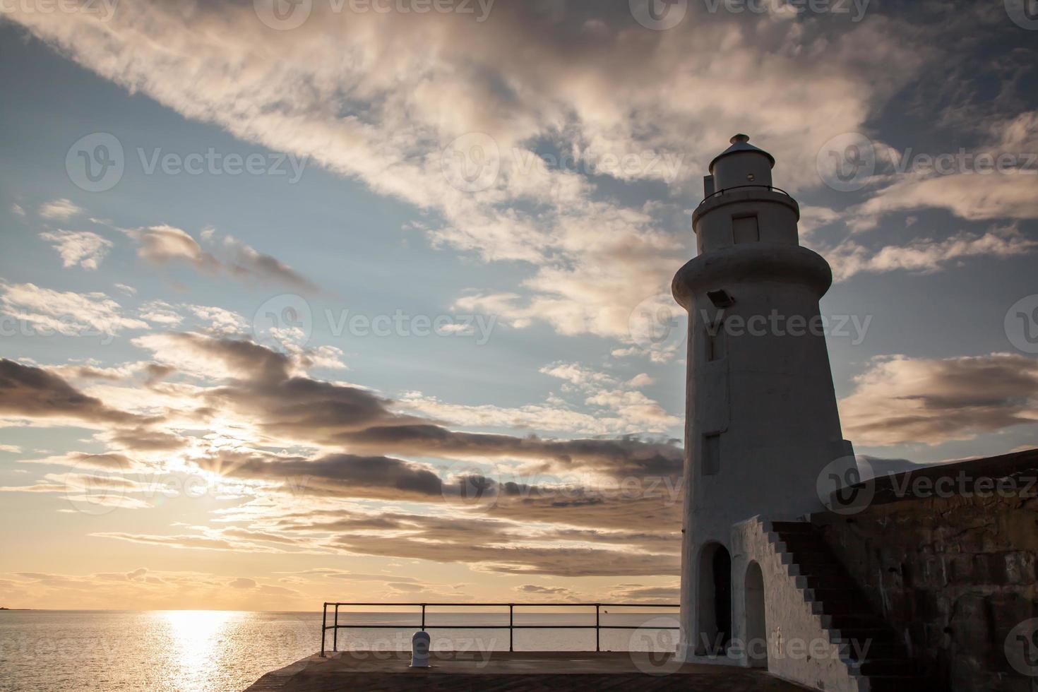 faro y puesta de sol sobre el mar foto