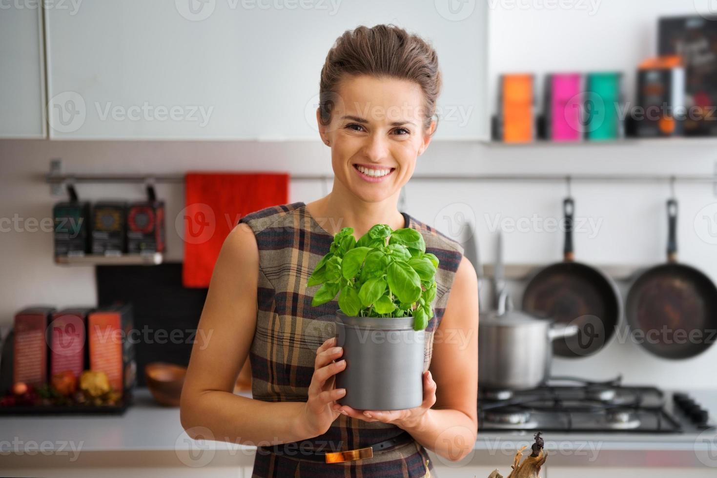 Mujer sonriente en la cocina con olla de albahaca fresca foto