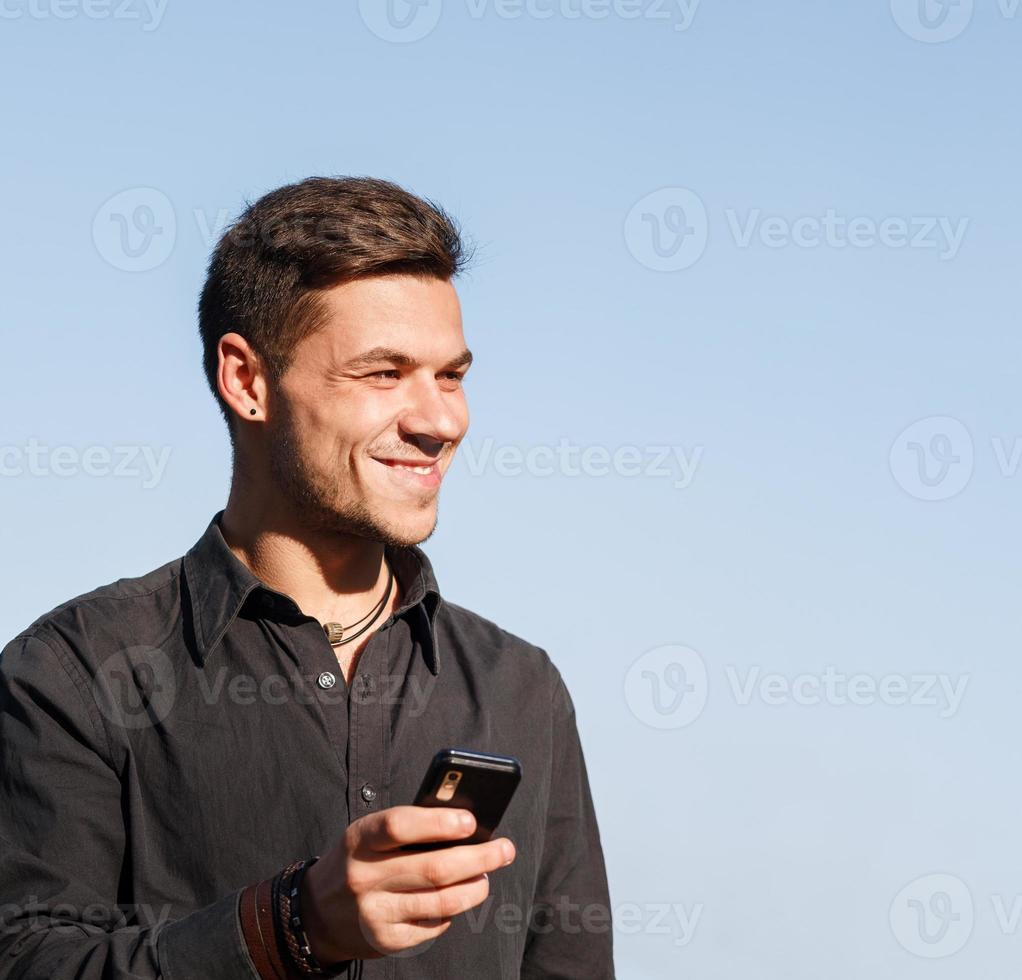 young male holding cellphone photo