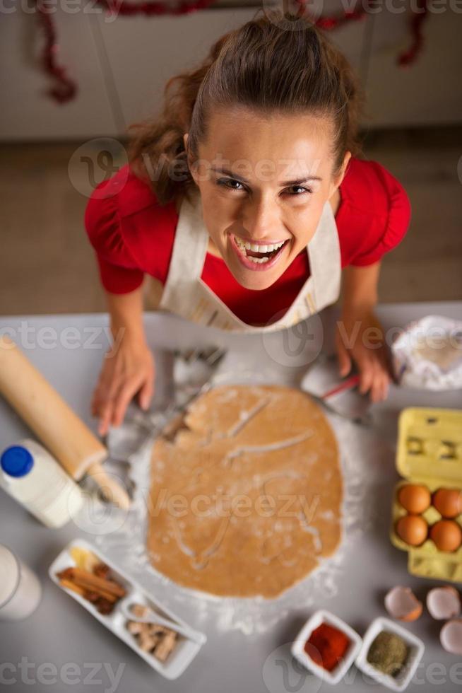 Ama de casa moderna haciendo galletas temáticas de Navidad en la cocina foto