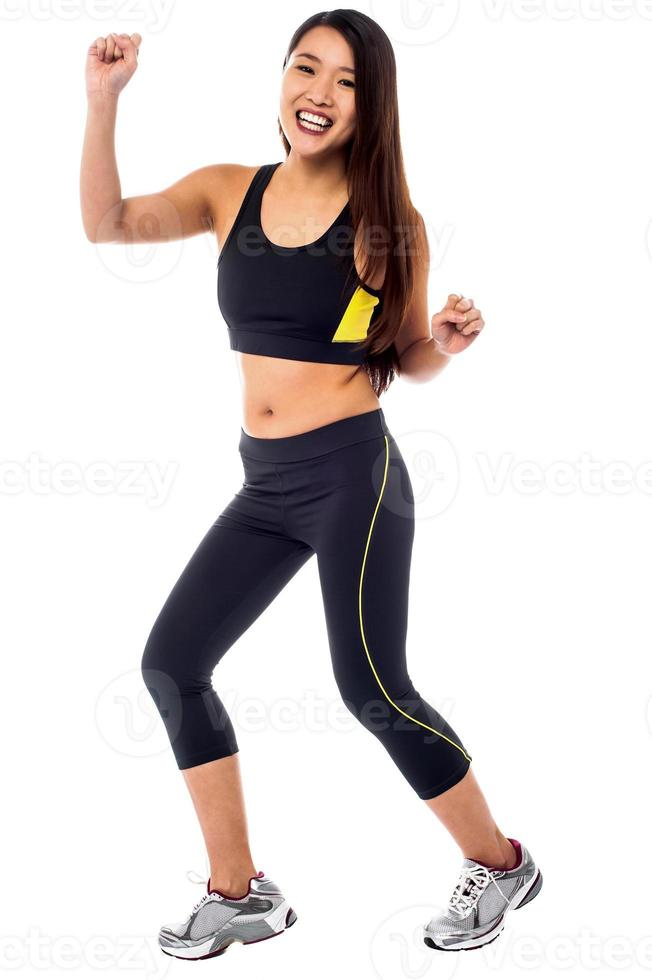 Cheerful fitness trainer dancing in joy photo