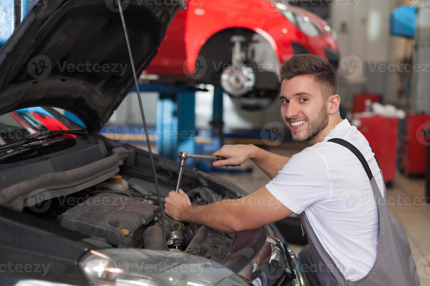 Cheerful mechanic using a ratchet wrench photo