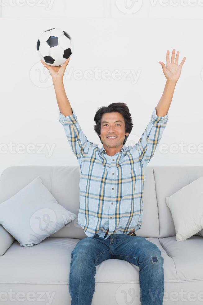 aficionado al fútbol animando mientras mira televisión foto