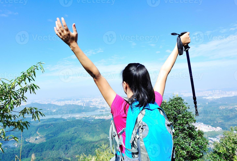 cheering hiking woman at mountain peak photo