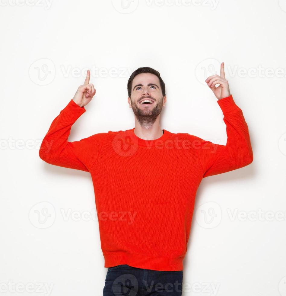 Cheerful young man pointing fingers up photo