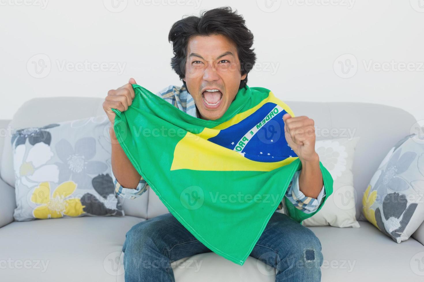 aficionado al fútbol brasileño animando mientras ve la televisión foto