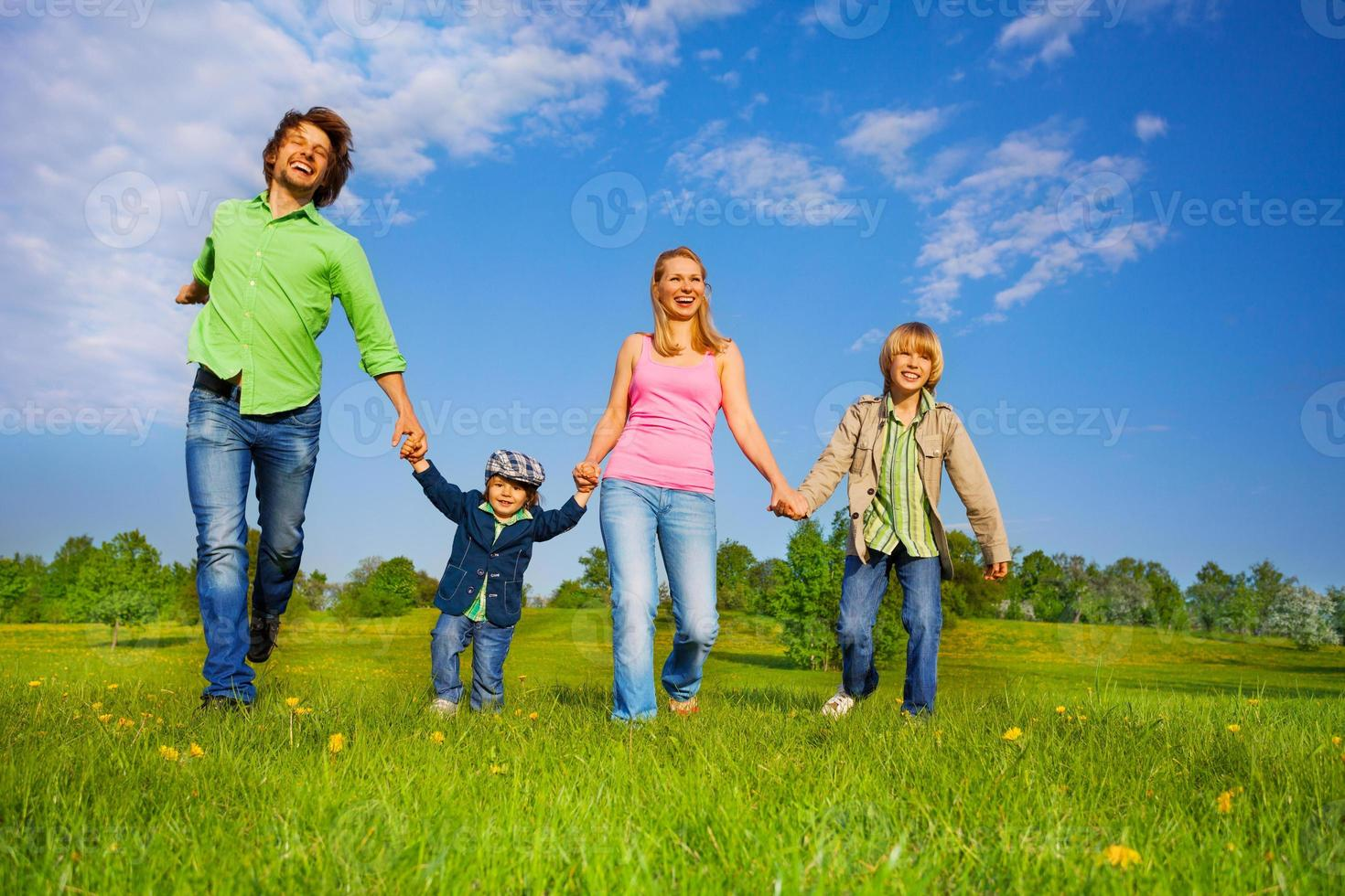 Cheerful parents walking with boys in park photo