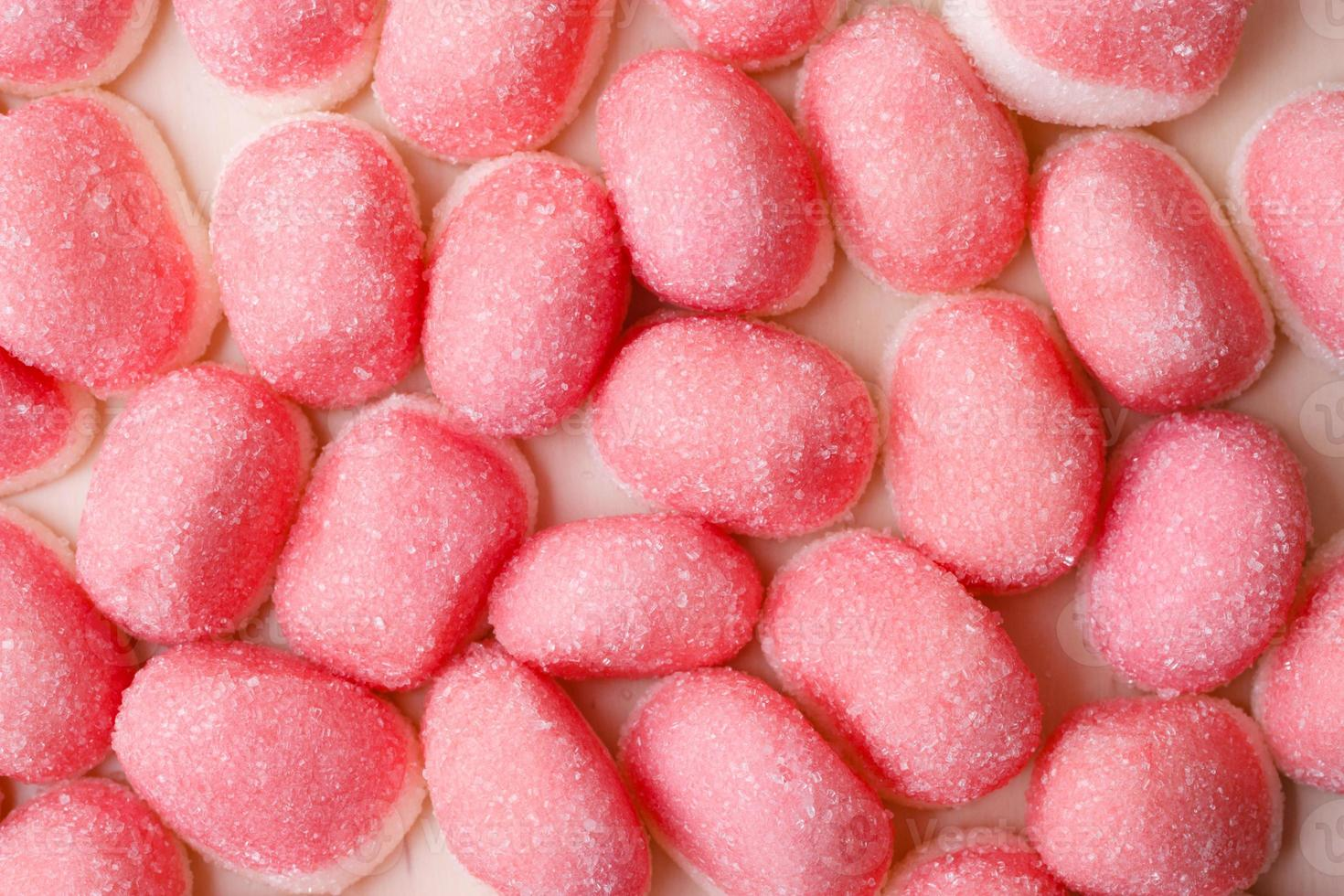 Pink jellies or marshmallows as background photo