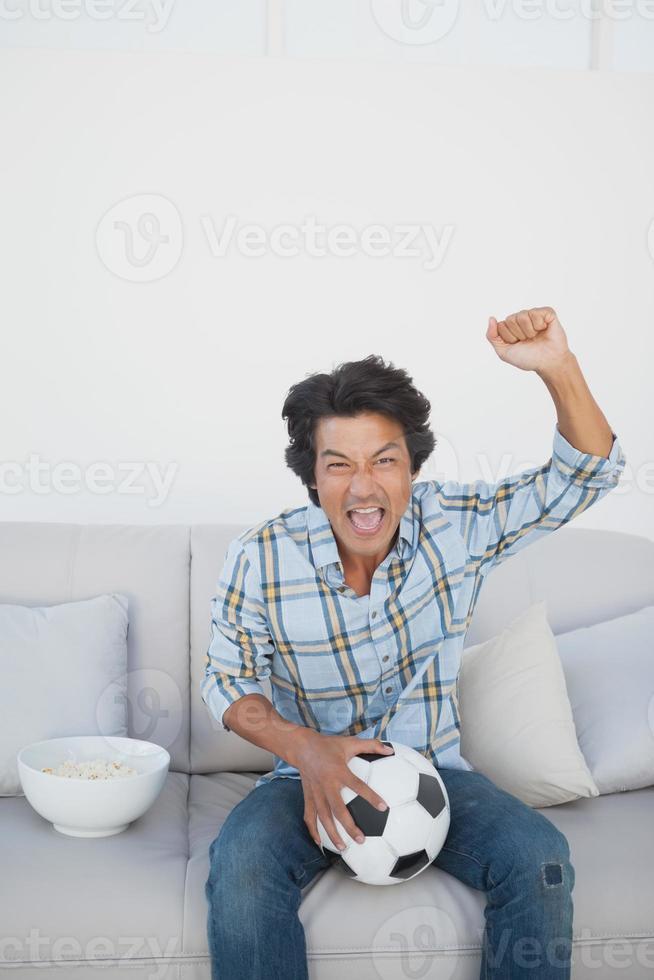 fanático del fútbol feliz animando mientras mira televisión foto