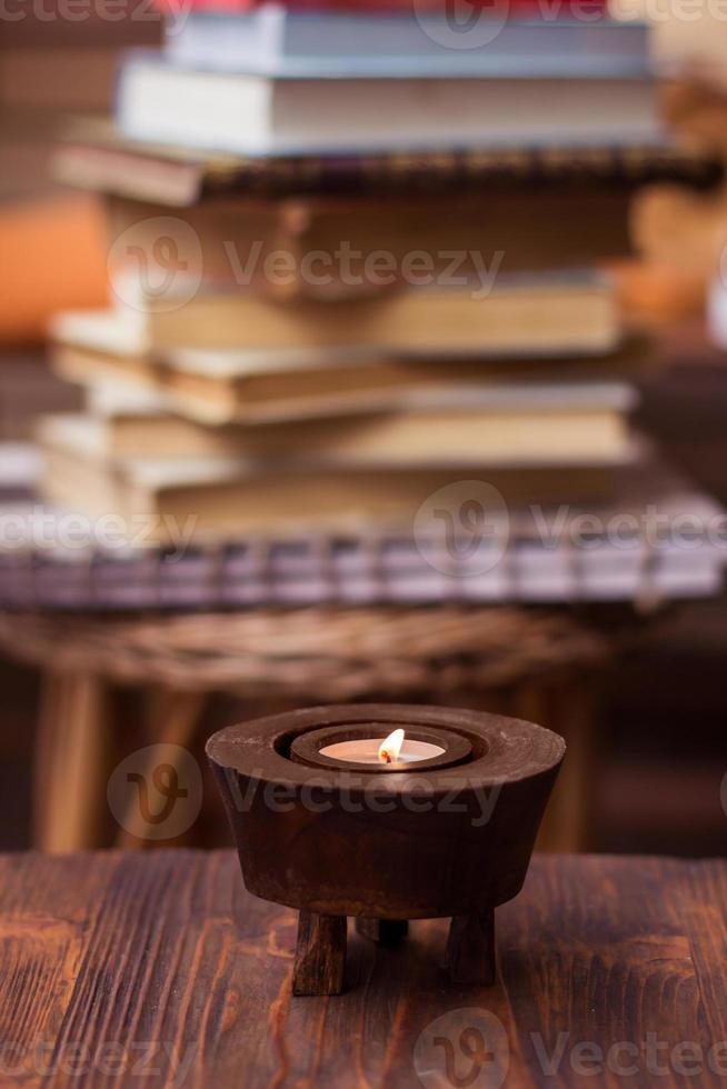 Candle on wooden table with books in background photo