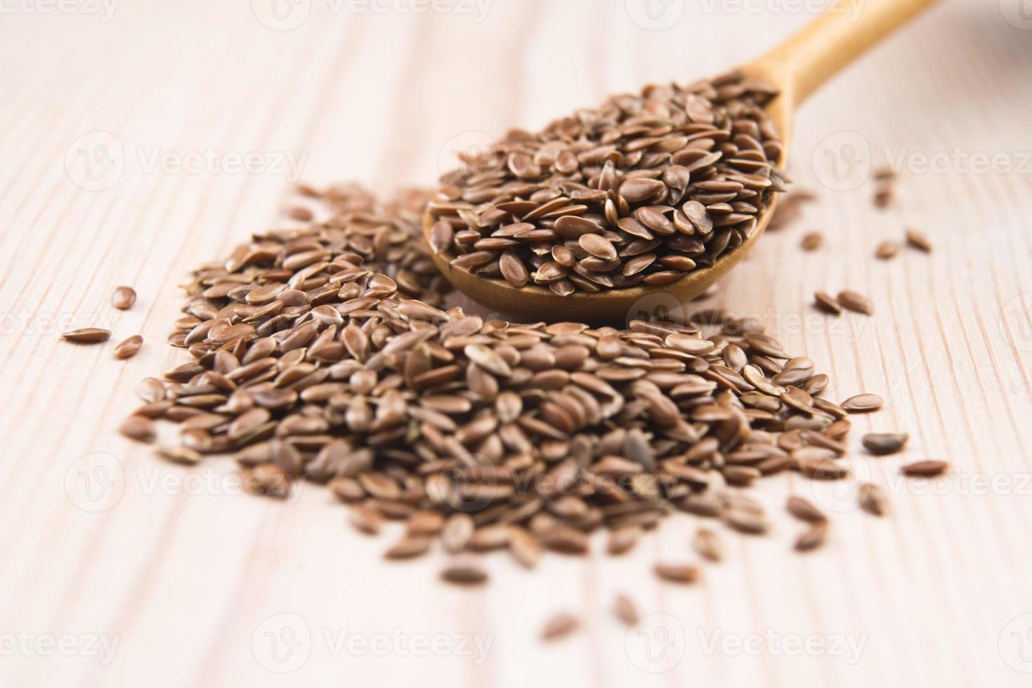 aceite de linaza y semillas de lino sobre fondo de madera foto