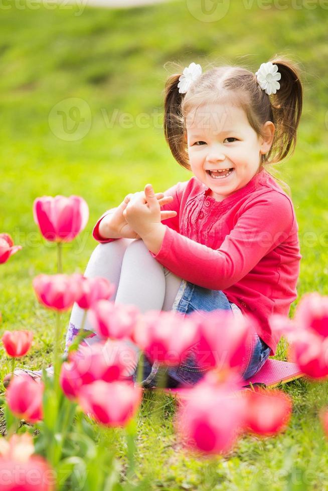 alegre niña sentada en la hierba mirando tulipanes foto
