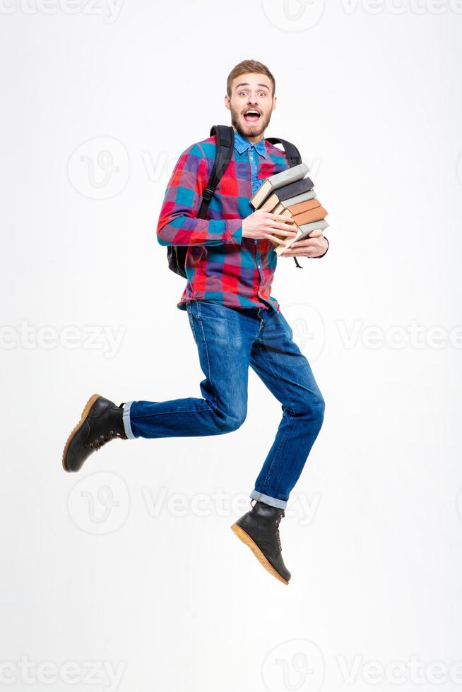 Happy cheerful student with backpack holding books and jumping photo